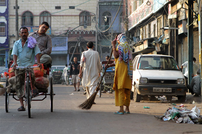 A woman sweeps a street in Old Delhi as a rickshaw driver transports a passenger.