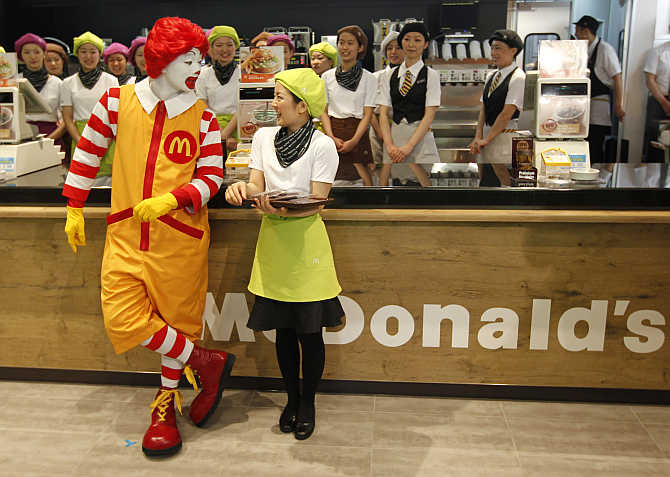 McDonald's 'Ronald McDonald' character chats with a counter staff in Tokyo, Japan.