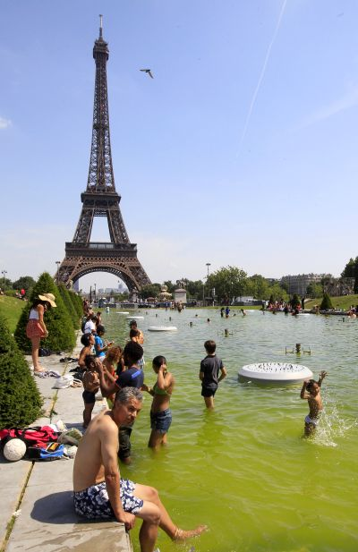 Tourists cool off in the Trocadero fountains near the Eiffel tower on a hot summer day in Paris.