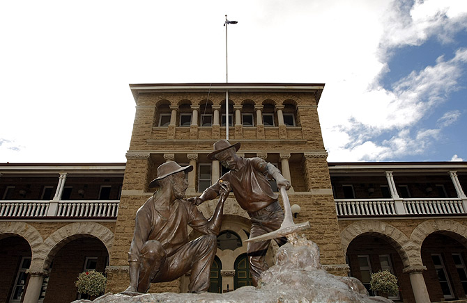 A statue which depicts miners striking gold stands in front of the Perth Mint.