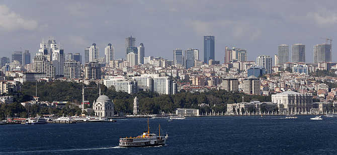 A ferryboat moves along the Bosphorus and past the city's skyscrapers in Istanbul, Turkey.