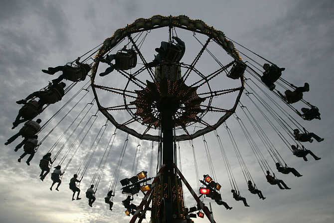 People ride a wave swinger at a carnival in Manila, the Philippines.