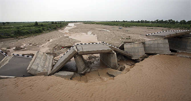 A bridge built over a stream leading to the river Tawi is damaged by flash floods on the outskirts of Jammu.