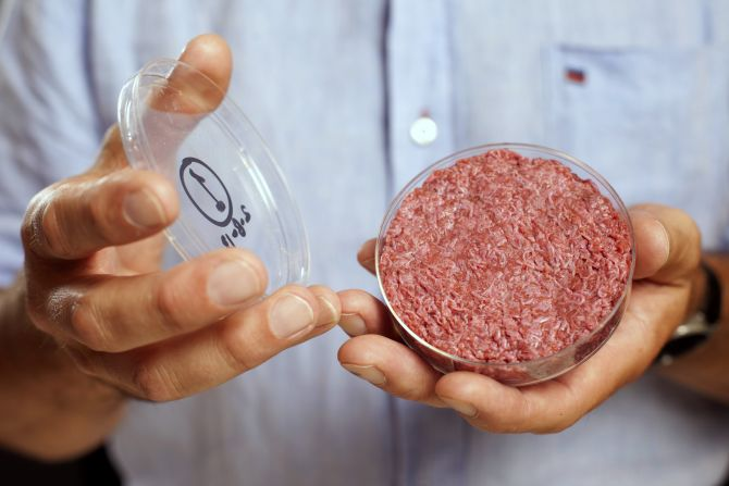 Professor Mark Post holds the world's first lab-grown beef burger during a launch event in west London.