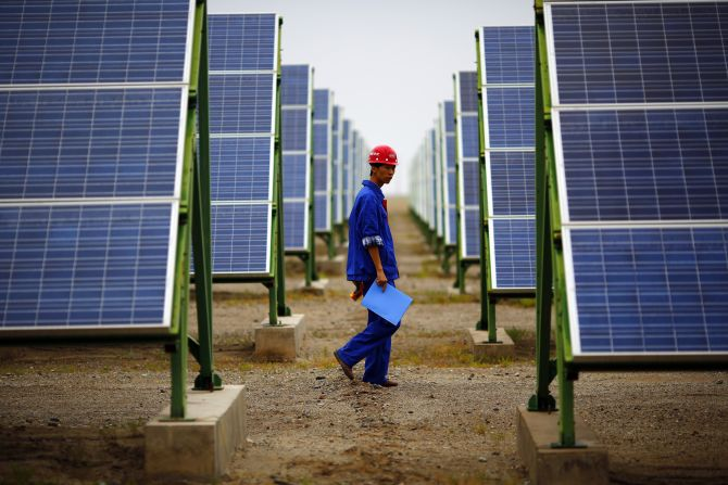 A worker inspects solar panels at a solar farm.