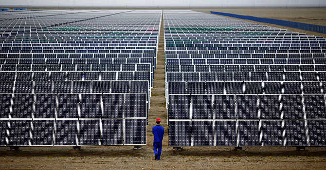 A worker inspects solar panels at a solar Dunhuang, 950km northwest of Lanzhou, Gansu Province, China. The two countries have also agreed to launch an initiative on clean energy.