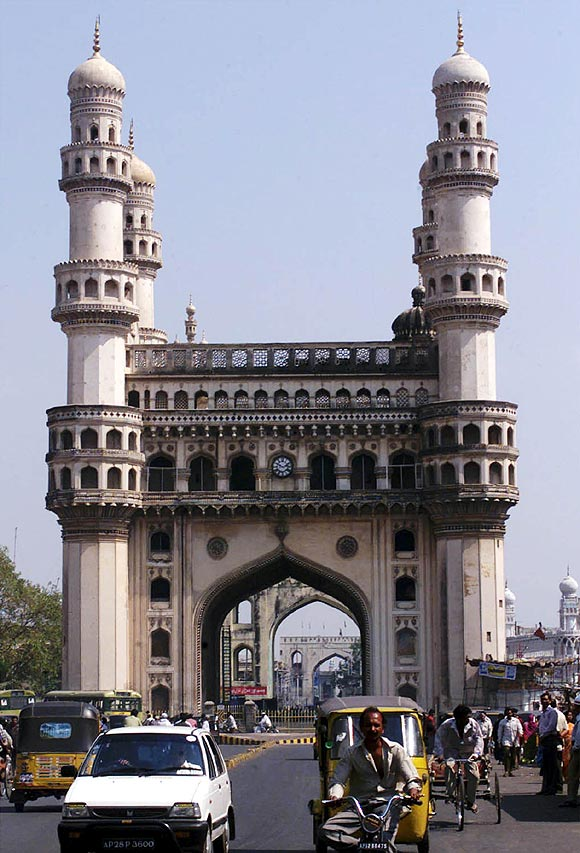 Residents of Hyderabad drive past the 'Charminar', the city's best known monument.