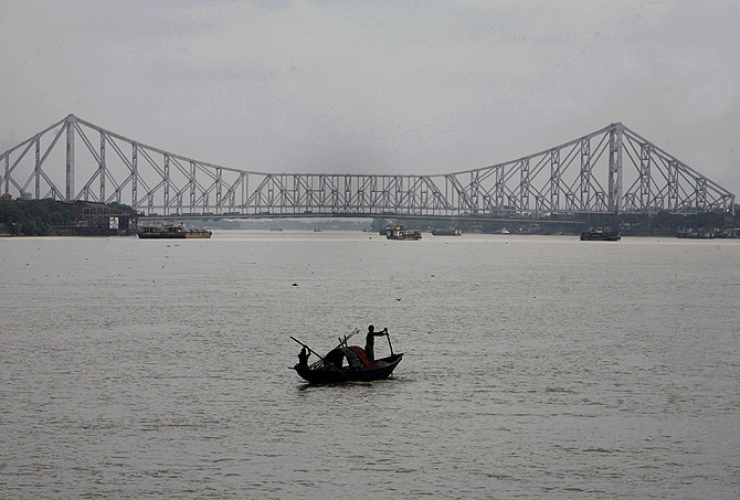 Fishermen row a boat on the Hooghly River against the backdrop of Howrah bridge in the eastern Indian city of Kolkata.