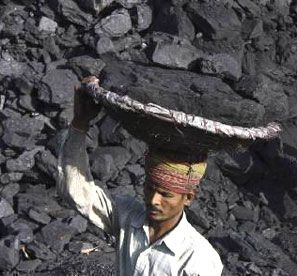 A labourer carries coal in a basket to load it in a truck. Photograph: Ajay Verma/Reuters