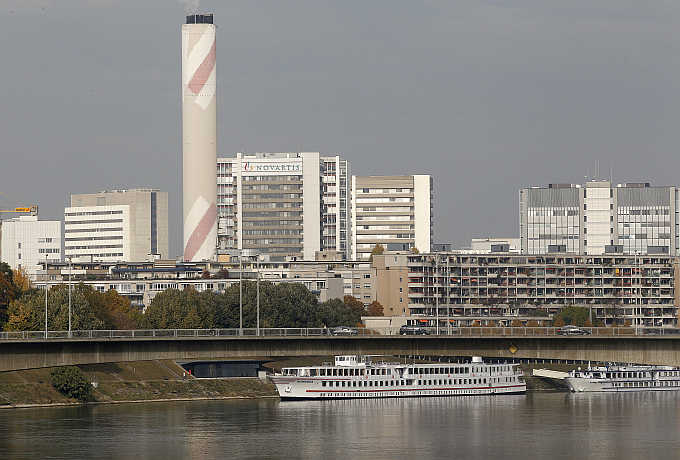 A view of the headquarters of Swiss drugmaker Novartis behind apartment buildings on the borders of the Rhine River in Basel.