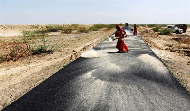 Women labourers throw dust on a road tarmac under construction at Bharadva village, Gujarat.