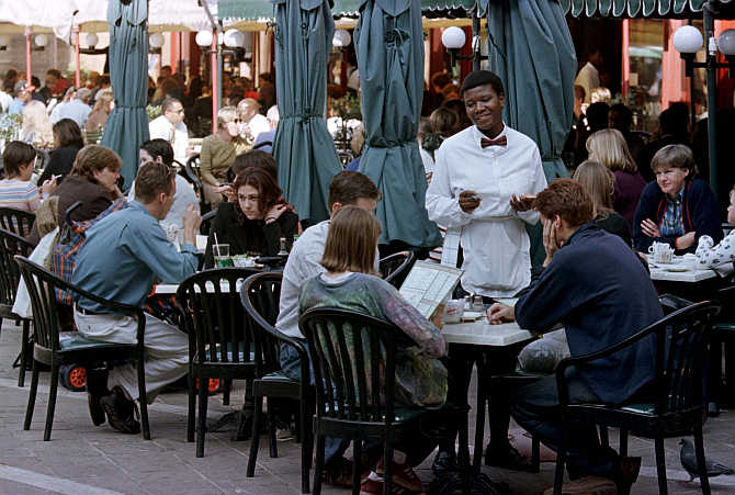 Tourists and South Africans enjoy a nice day as they eat lunch at a restaurant in Sandton square in Johannesburg, South Africa.