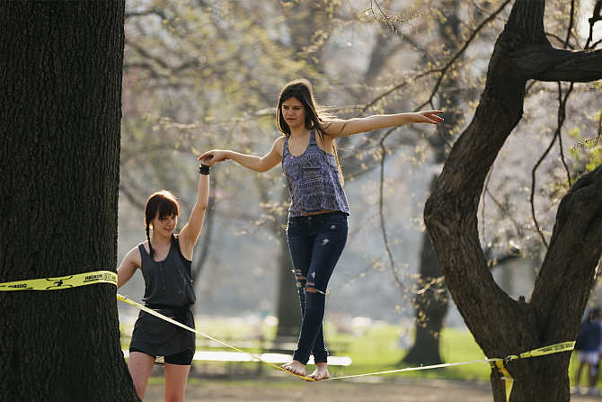 A woman practices walking on a slack-line at Central Park during a warm day in New York City, United States.