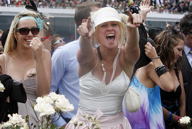 A race-goer celebrates after jockey Corey Brown rode Shocking to victory in the Melbourne Cup at Flemington racecourse in Melbourne, Australia.