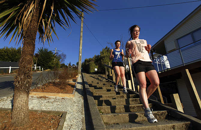Women run down Baldwin street in Dunedin, New Zealand. Baldwin street is considered as one of the steepest streets in the world.