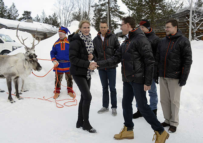 Prime Minister of Denmark Helle Thorning-Schmidt, left, greets her Finnish counterpart Jyrki Katainen, right, during the informal Lapland meeting in Saariselka, Finland.