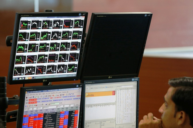A broker monitors a screen displaying live stock quotes on the floor of a trading firm in Mumbai.