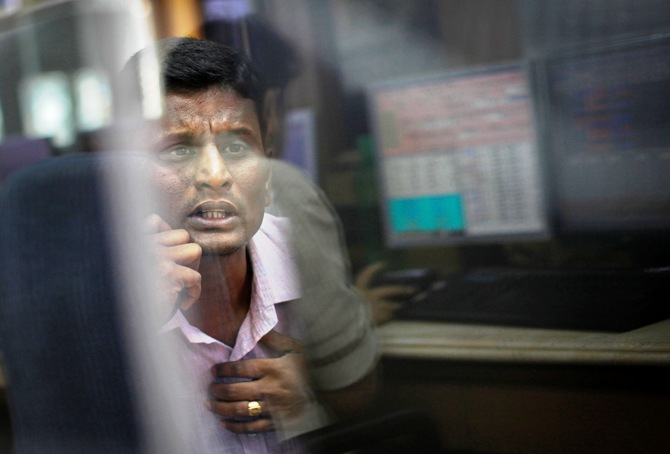 A broker looks at a computer screen as he talks on a phone at a stock brokerage firm in Mumbai.