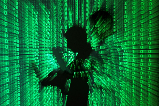An illustration picture shows a projection of binary code on a man holding a laptop.