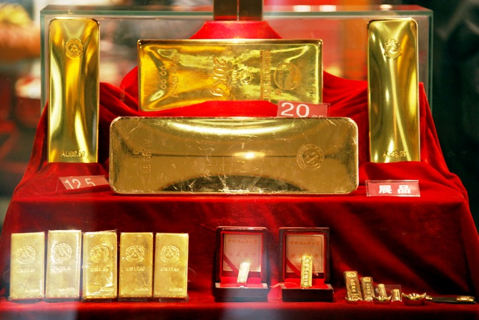 Gold bars of various sizes can be seen in a display case.