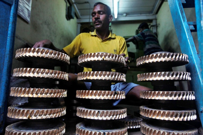 A worker cleans gear wheels used in conveyor belts at a small scale factory in Kolkata.