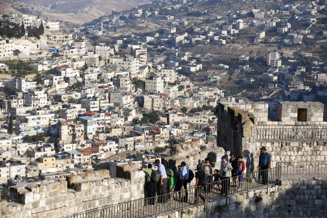 Arab neighbourhoods in East Jerusalem are seen in the background as tourists walk atop a wall surrounding Jerusalem's Old City.