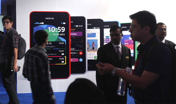 Visitors gather during the unveiling of Nokia's $99 phone in its mid-range Asha line.