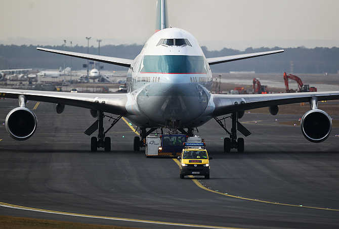 An airport apron controller vehicle is pictured in front of a Cathay Pacific Boeing B747-400 Aircraft on the runway at Frankfurt's airport, Germany.