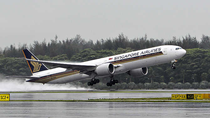 A Singapore Airlines Boeing 777-300ER passenger jet takes off in the rain at Changi Airport in Singapore.