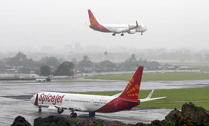 SpiceJet aircraft prepare for landing and take-off in Mumbai.