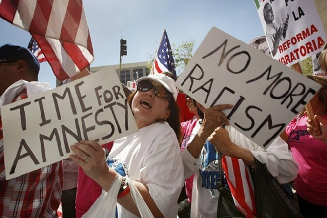 Marchers carry signs in support of immigrant rights as thousands of protesters march up Broadway during a May Day immigration rally in Los Angeles, California.