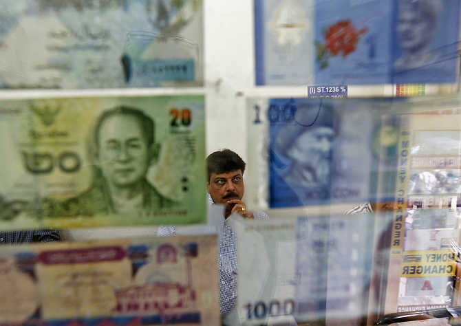 A man watches television inside his currency exchange shop in New Delhi.