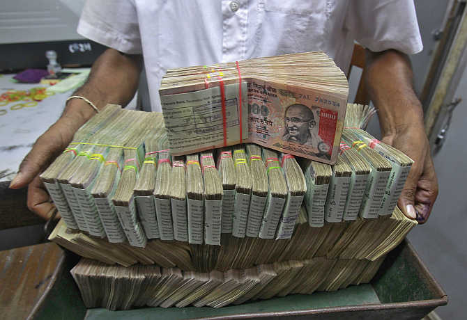 An employee poses with the bundles of rupee notes inside a bank in Agartala, Tripura.