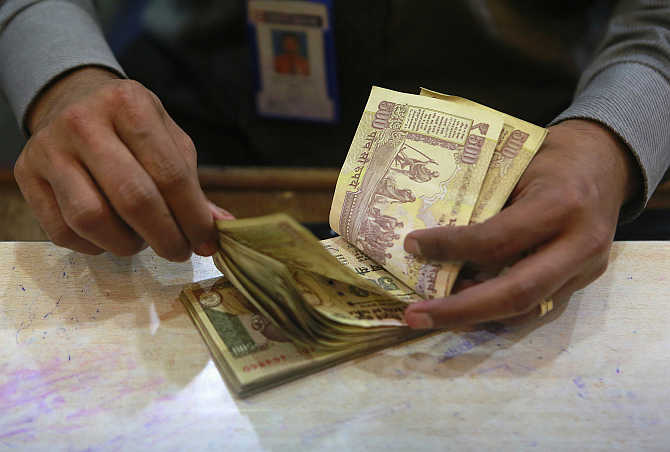 A cashier counts rupee notes inside a bank in Mumbai.