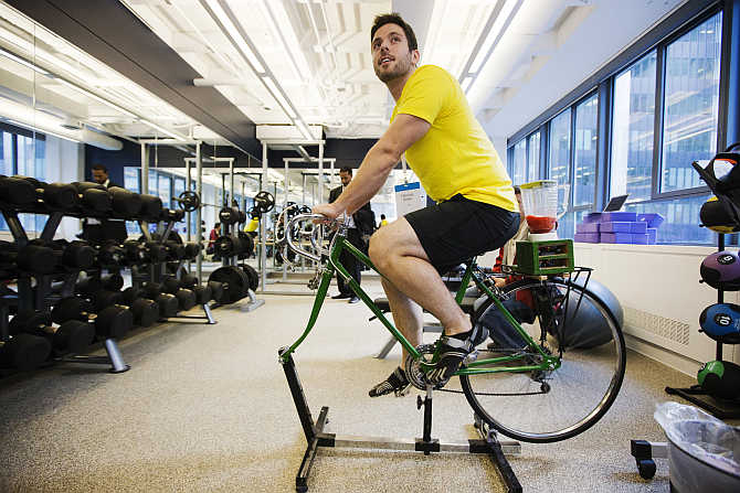 An employee demonstrates the use of an exercise cycle, that powers a blender making a fruit smoothie, inside the gym at the Google office in Toronto, Canada.