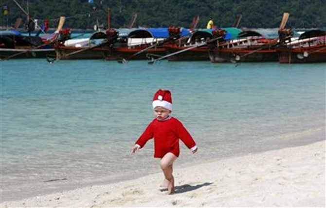 A boy wearing a Santa hat runs on a beach past taxi boats in TurataoMarineNational Park in southern Thailand's Satun province