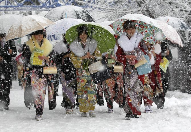 Japanese women in kimonos walk to attend a ceremony celebrating Coming of Age Day in heavy snowfall at Toshimaen amusement park in Tokyo.