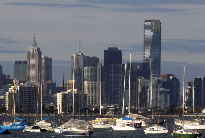 Sailboats and yachts are seen in front of the Melbourne skyline.