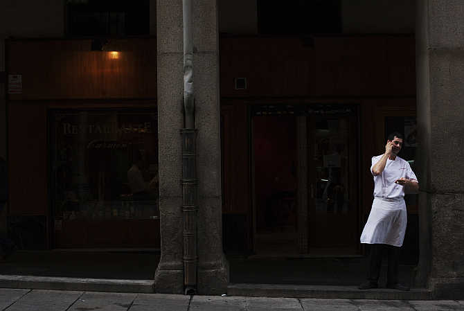 A cook takes a break as he talks on the phone in central Madrid, Spain.