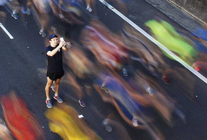 A man takes a picture of himself among participants during the annual City2Surf fun run in central Sydney, Australia.