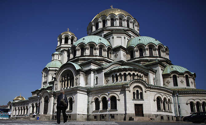 A woman walks past the golden-domed Alexander Nevski cathedral in central Sofia, Bulgaria.