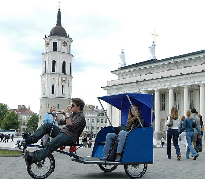 A man drives a city resident in a Velomobile outside the cathedral in Vilnius, Lithuania.