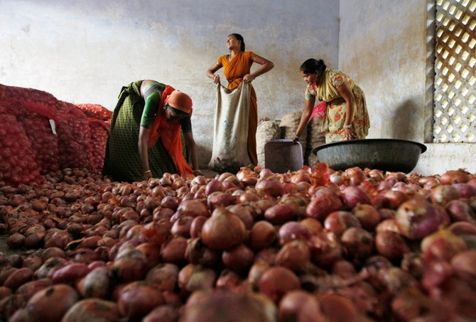 Workers fill sacks with onions after sorting them at a wholesale market in Ahmedabad.