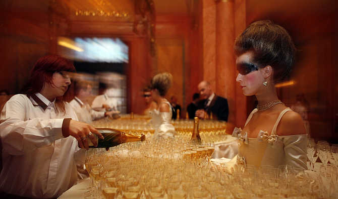 A waitress pours champagne into glasses at the foyer of Municipal House before the final of the Elite Model Look competition in Prague, the Czech Republic.