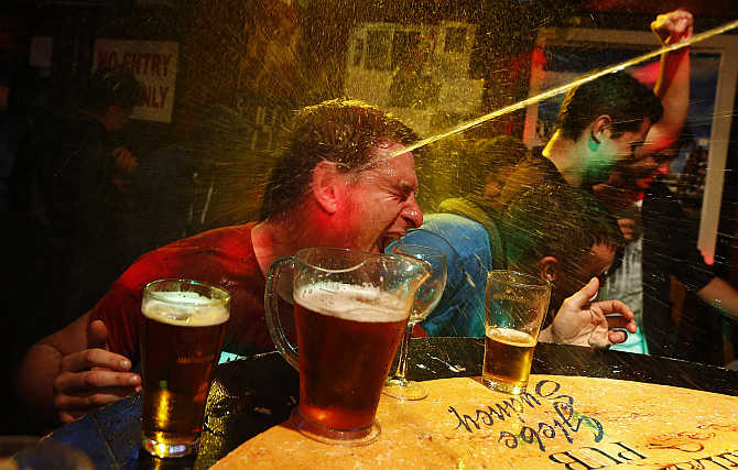 A party goer is splashed with water after winning a crab race at a pub called the 'Friend in Hand' in central Sydney, Australia.