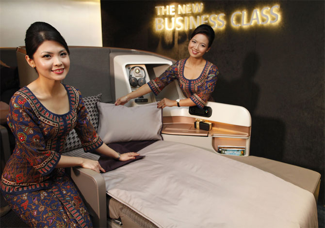 Singapore Airlines Ltd stewardesses pose next to a business class seat during the launch of their new generation of cabin products at Changi Airport in Singapore.