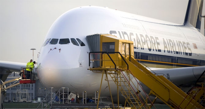 Airbus employees work at an Airbus A380 aircraft of 'Singapore Airlines' at the Airbus facility in Finkenwerder near Hamburg.
