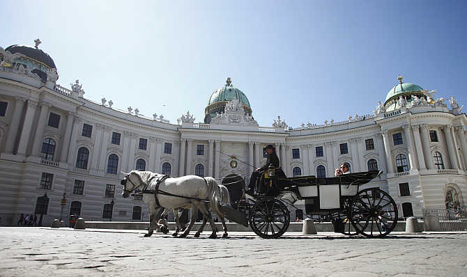 A Fiaker horse carriage passes Hofburg palace during a sunny spring day in Vienna, Austria.