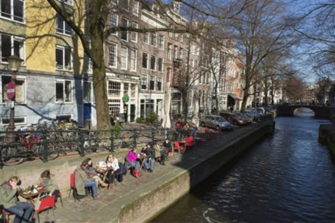 People sit on a quay at the Leliegracht canal in Amsterdam.