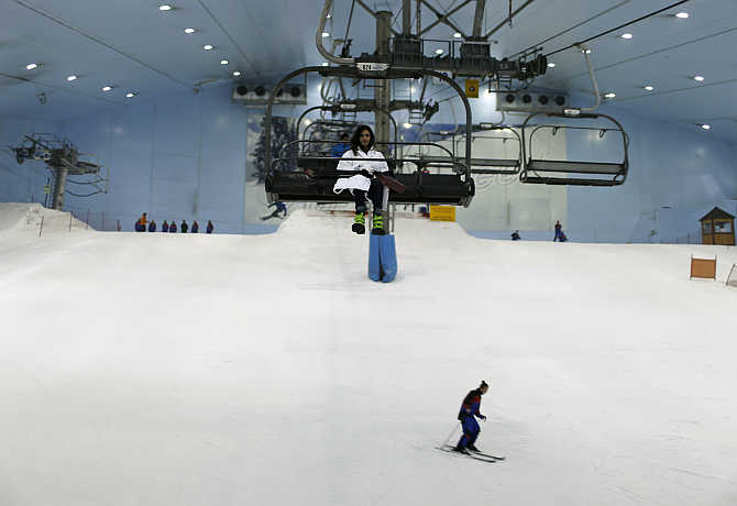 Visitors ski and ride in chairlifts in mountain-themed ski park at Emirates Mall in Dubai, United Arab Emirates.